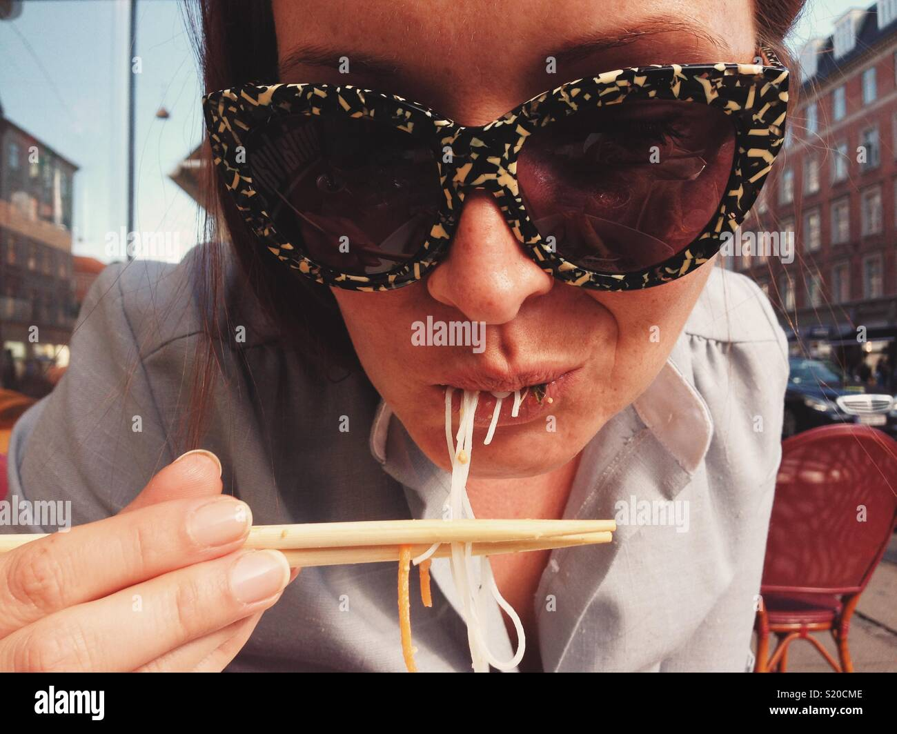 Woman in sunglasses eating noodles with chopsticks - Stock Image