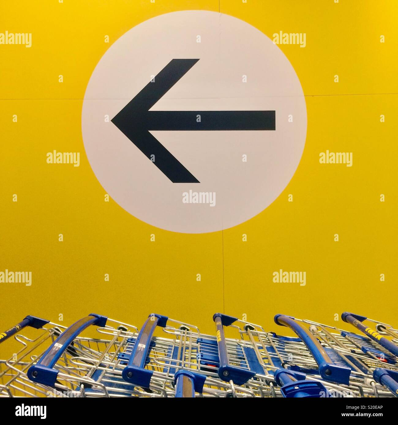 IKEA shopping trolleys and arrow sign - Stock Image