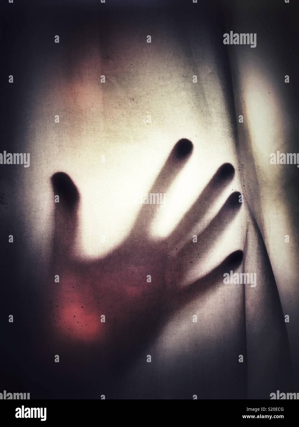 A silhouette of an outstretched hand against a see through fabric Stock Photo