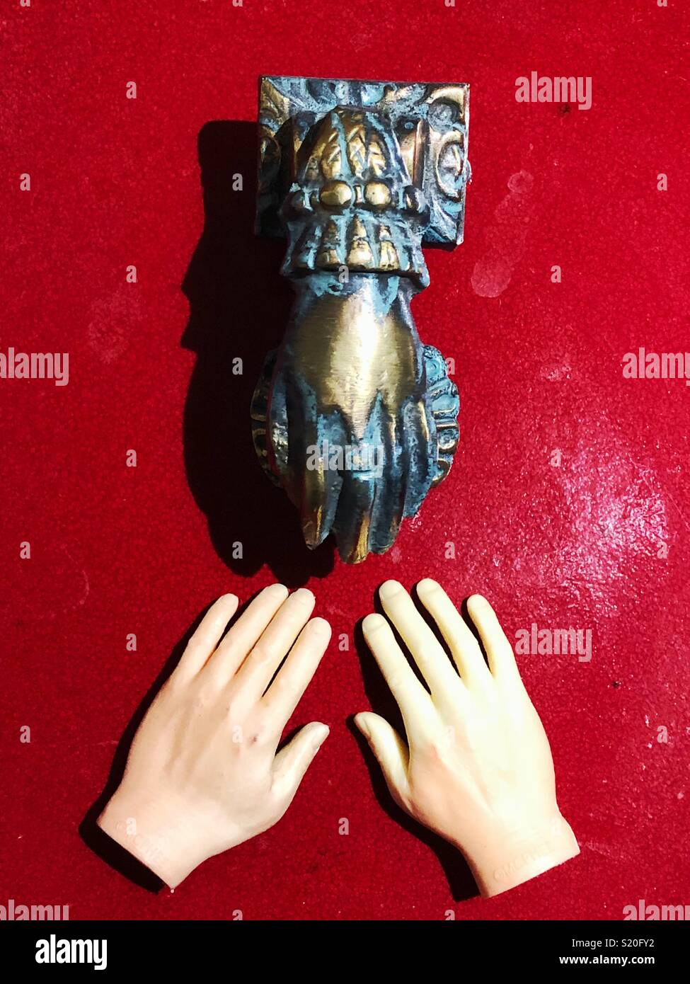 Two plastic finger toy hands in front of bronze hand shaped door knocker on red background - Stock Image