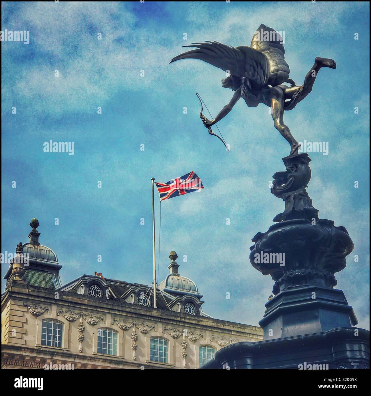 A Statue Of Anteros or The Angel of Christian Charity that sits atop the Shaftesbury Memorial Fountain in Piccadilly Circus, London. Or possibly Eros has shot an arrow at The Union Jack Flag?! © C.H. - Stock Image