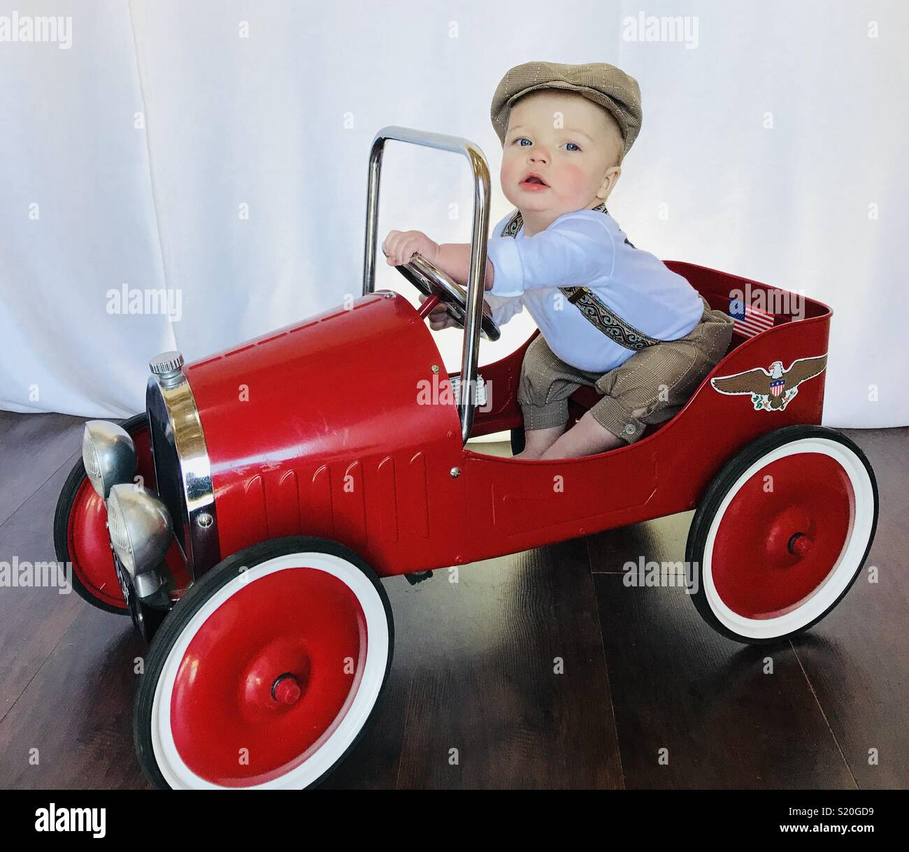 Cute baby in a news boy outfit playing with his antique looking peddle car. This cute baby wears brown tan knickers, suspenders and a news boy hat while he sits in his red car pretending to drive. - Stock Image