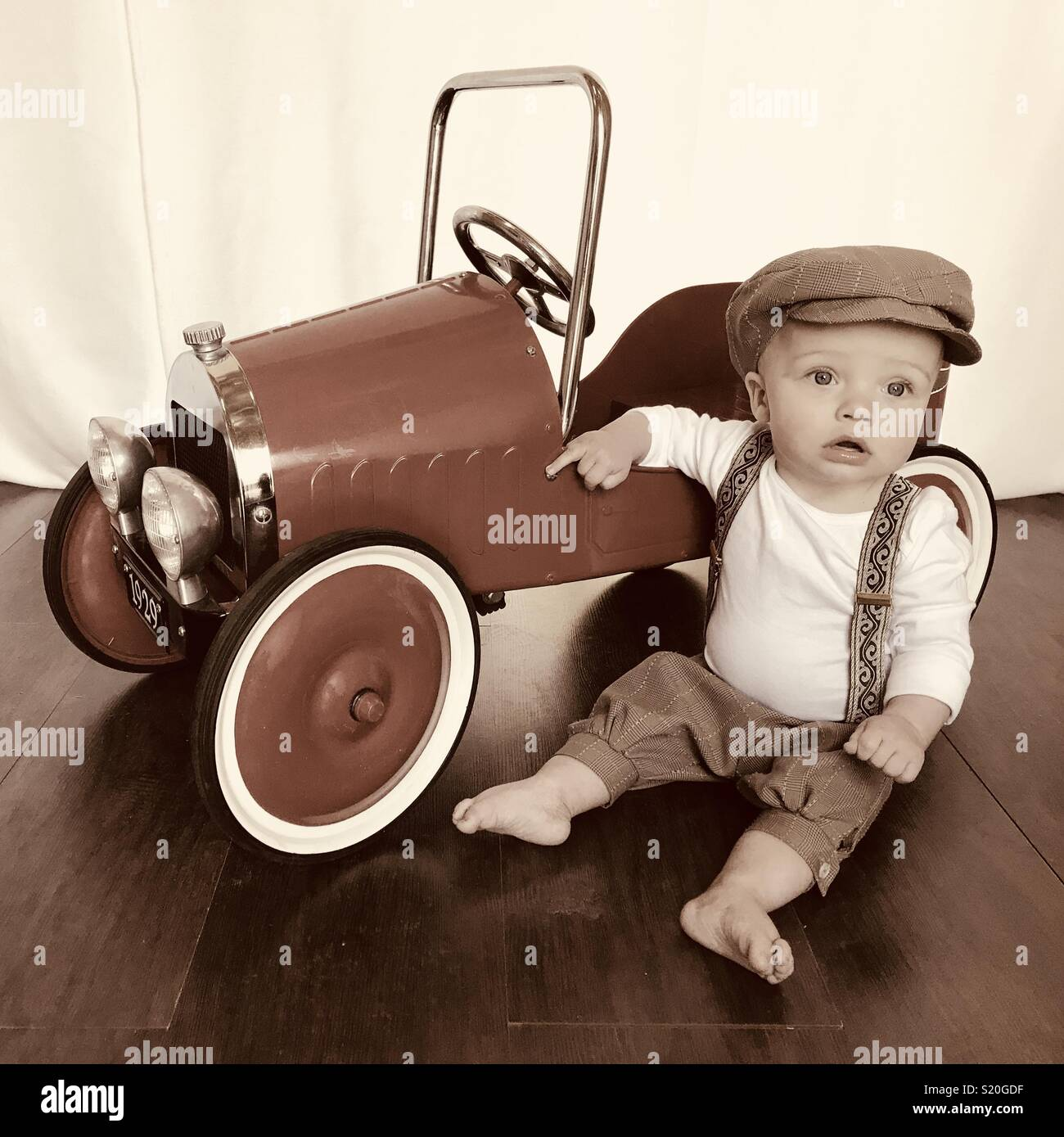 2073ec26f26ef Cute baby in a news boy outfit playing with his antique looking peddle car.  This