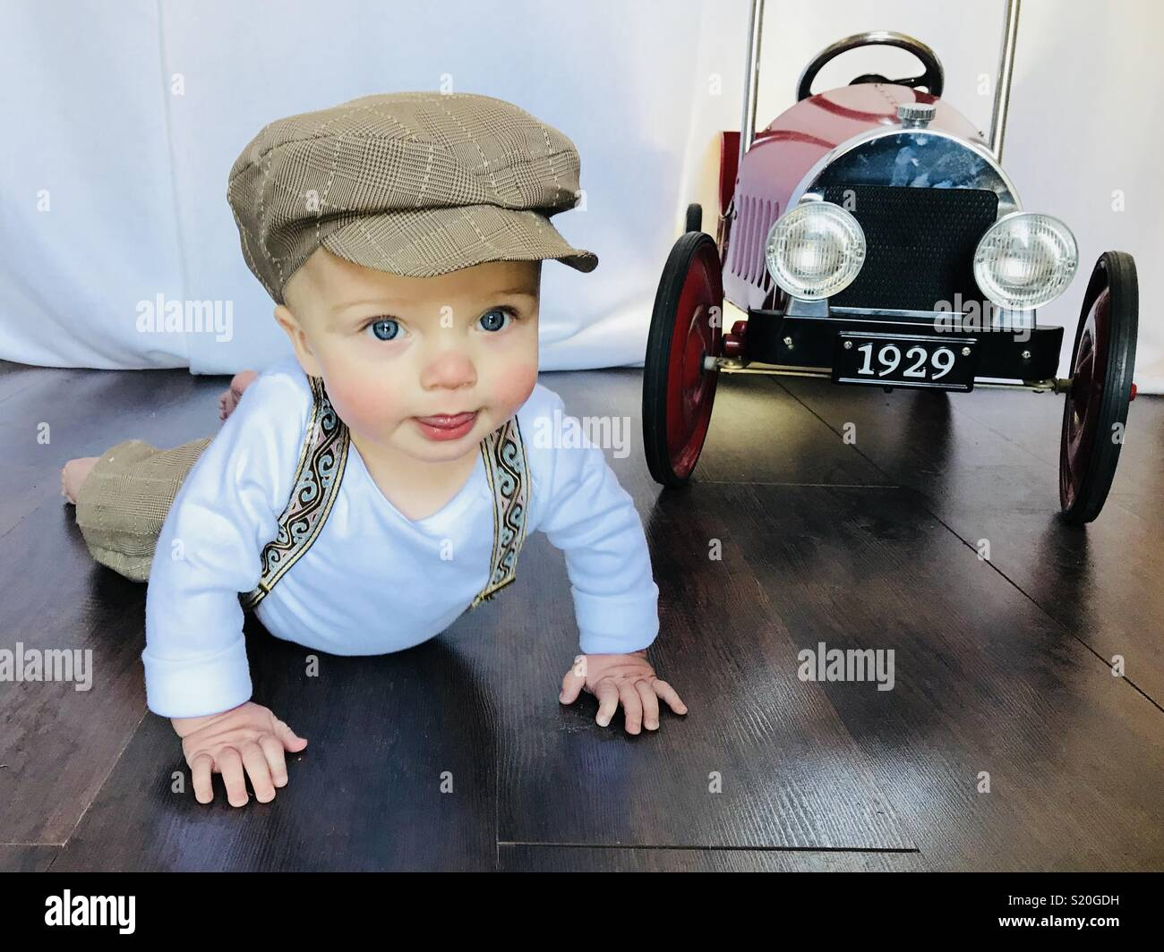 Cute baby in a news boy outfit playing with his antique looking peddle car. This cute baby wears brown tan knickers, suspenders and a news boy hat while crawling beside his car. - Stock Image