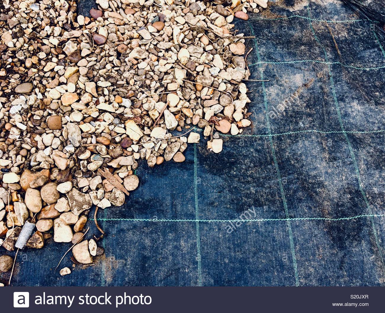 Weed control fabric with gravel on top - Stock Image