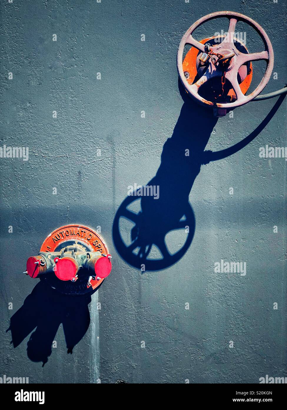 Fire house attachment and turning wheel on the wall with long shadows - Stock Image