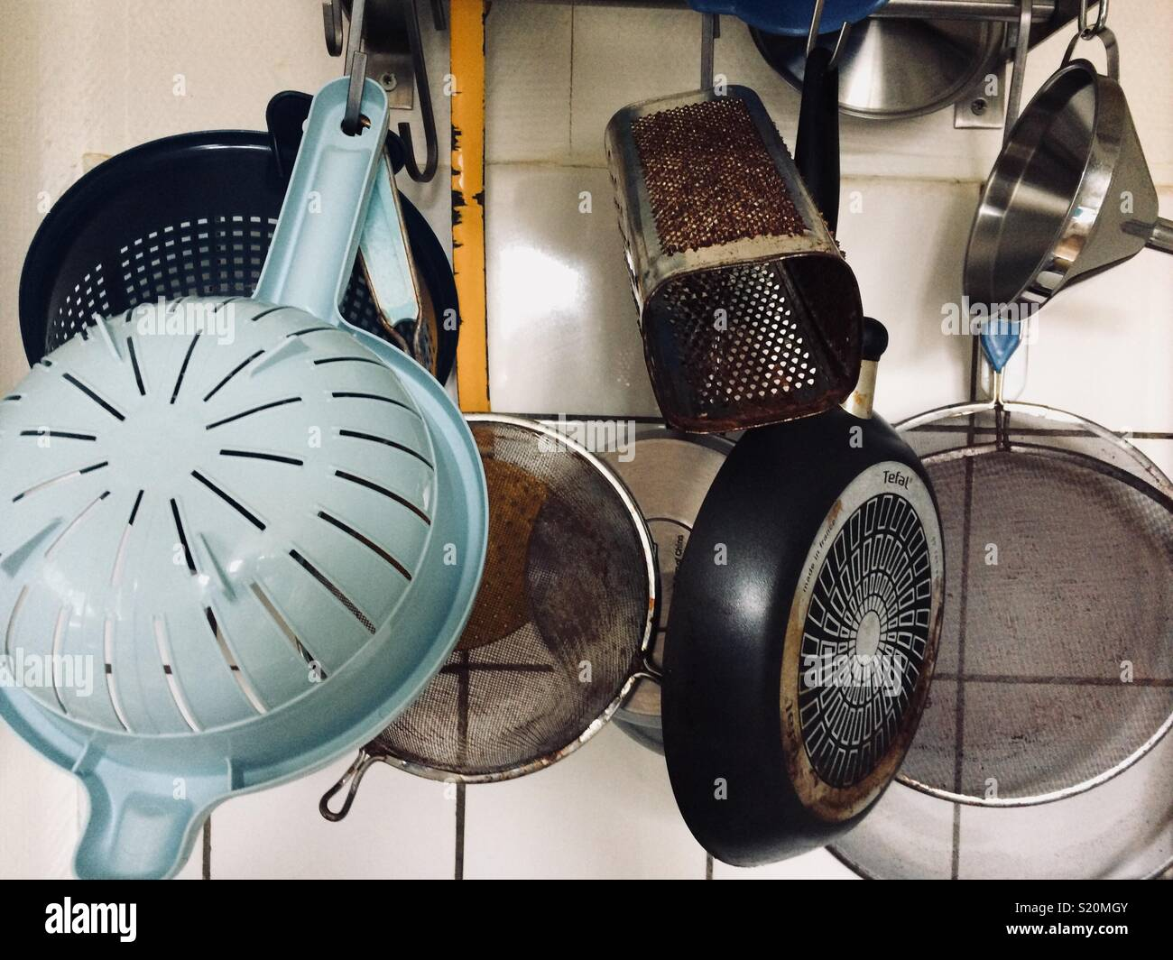 Kitchen utensils hanging in a kitchen - Stock Image