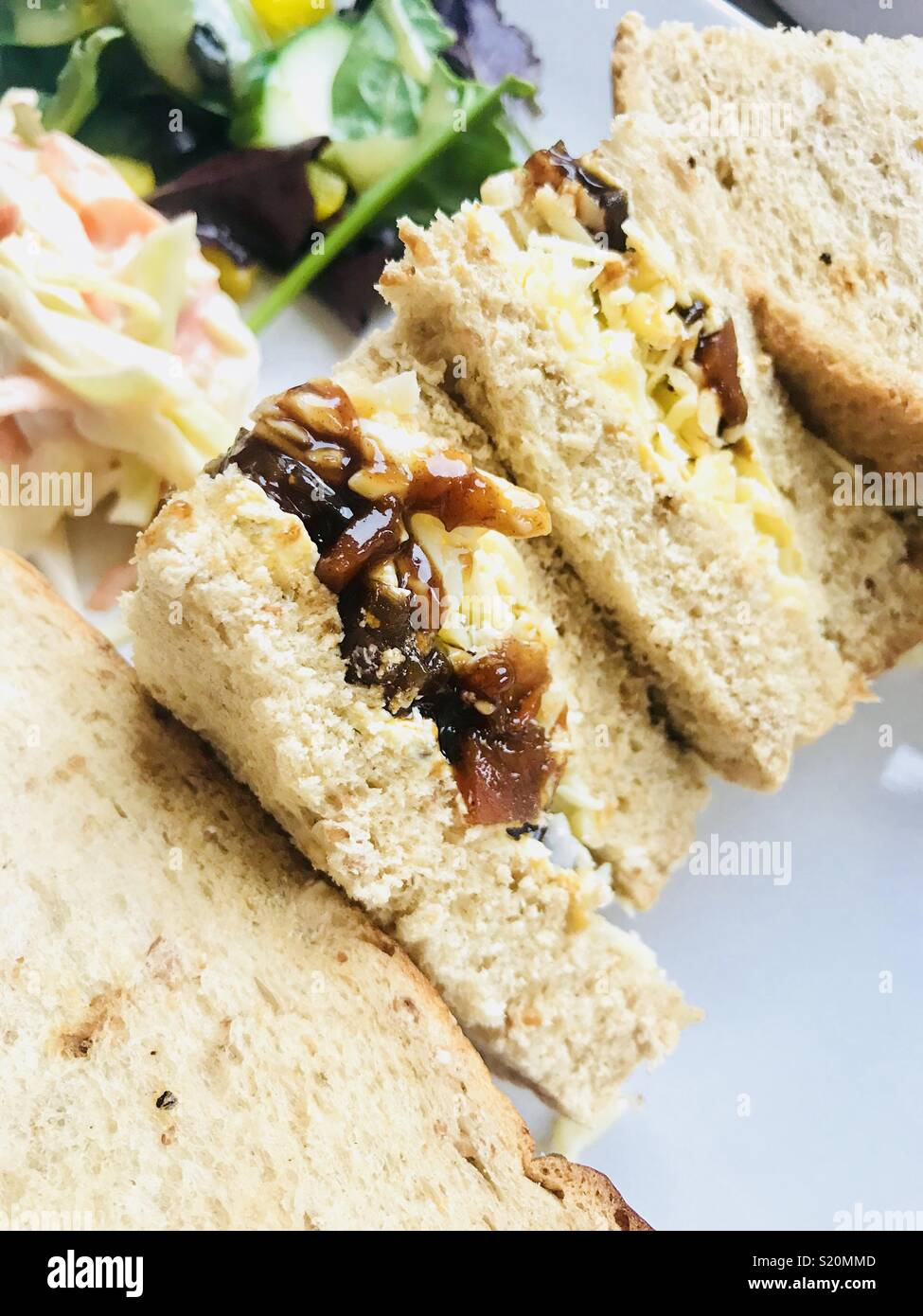 Cheese and pickle brown bread sandwich with side salad - Stock Image