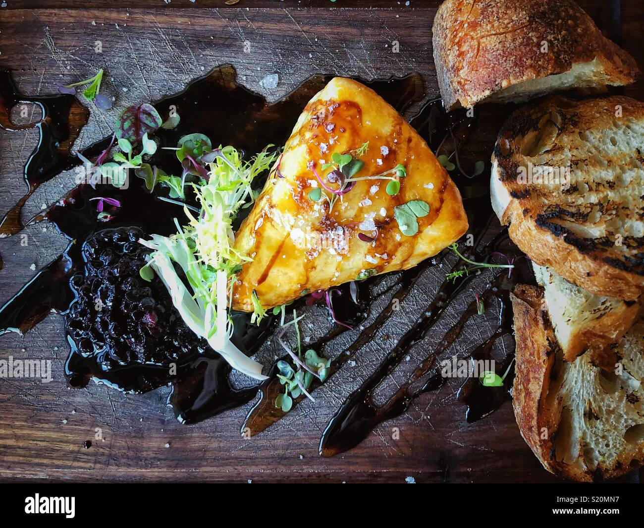 Baked brie wedge on a dark wood serving board with toasted bread and wild blueberry compote - Stock Image