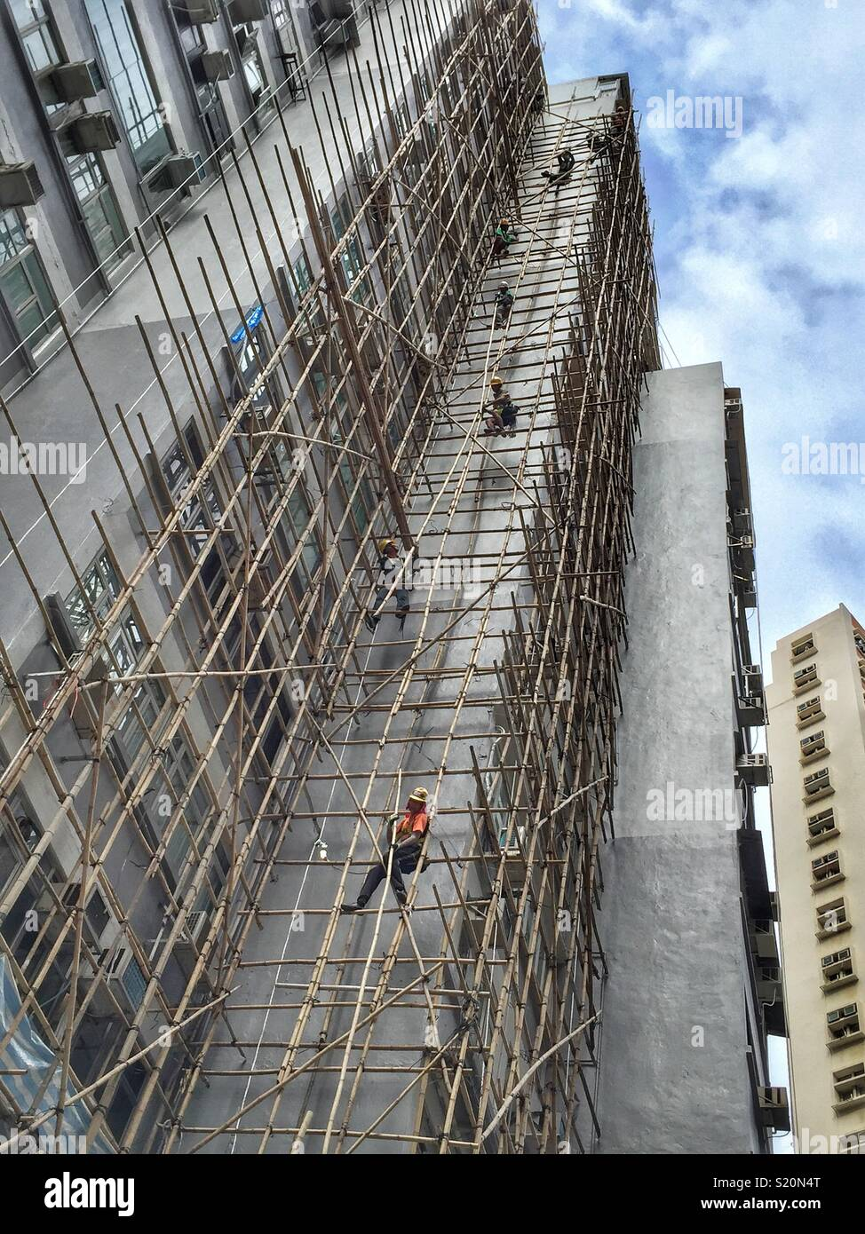 Workmen form a human chain to dismantle bamboo scaffolding after renovations on a highrise residential building in Wan Chai, Hong Kong Island - Stock Image
