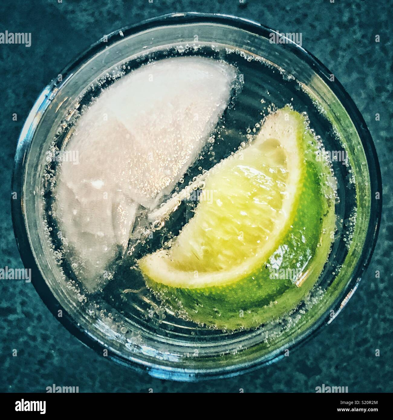 Top view of single ice cube and lime wedge in a glass of sparkling water - Stock Image