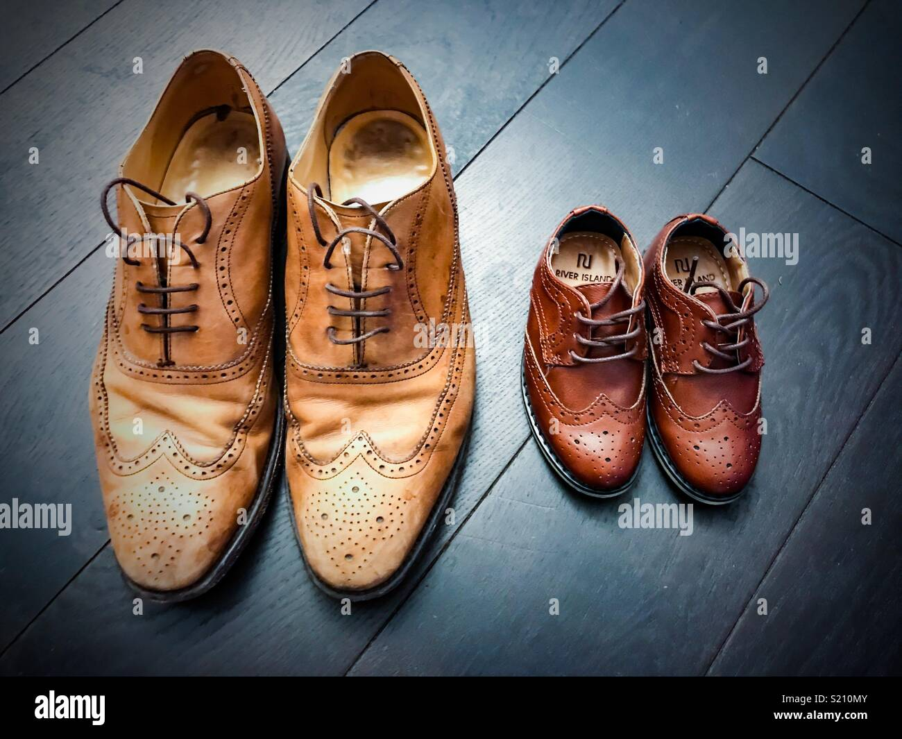 Like father like son. Kids shoes and dad shoes - Stock Image