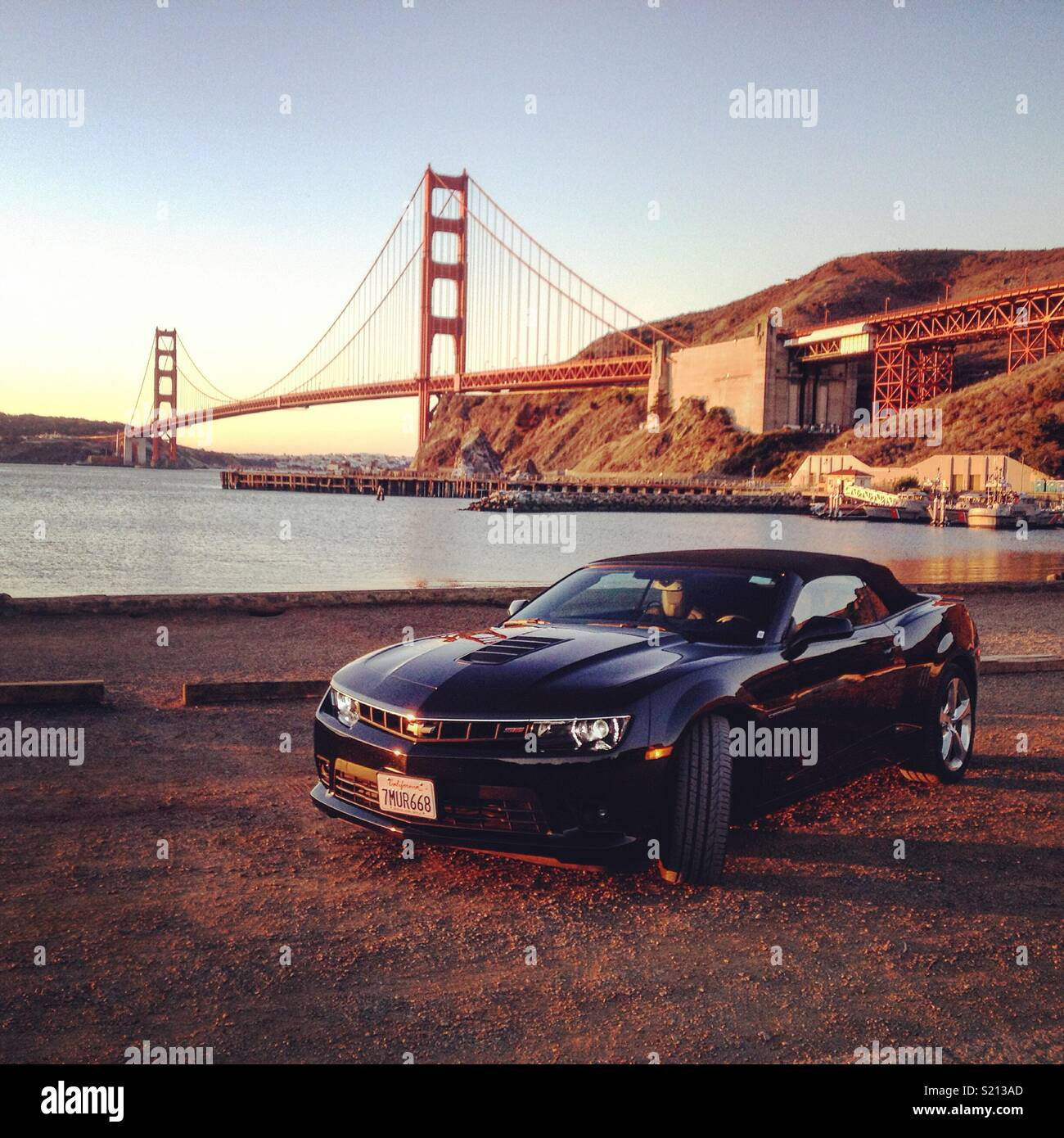 Chevrolet Camaro SS Convertible in front of the Golden Gate Bridge in late November as the sun rises - Stock Image