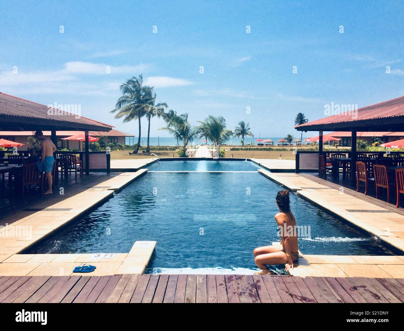 Relaxing by the pool at Kendeja beach resort in Monrovia - Stock Image