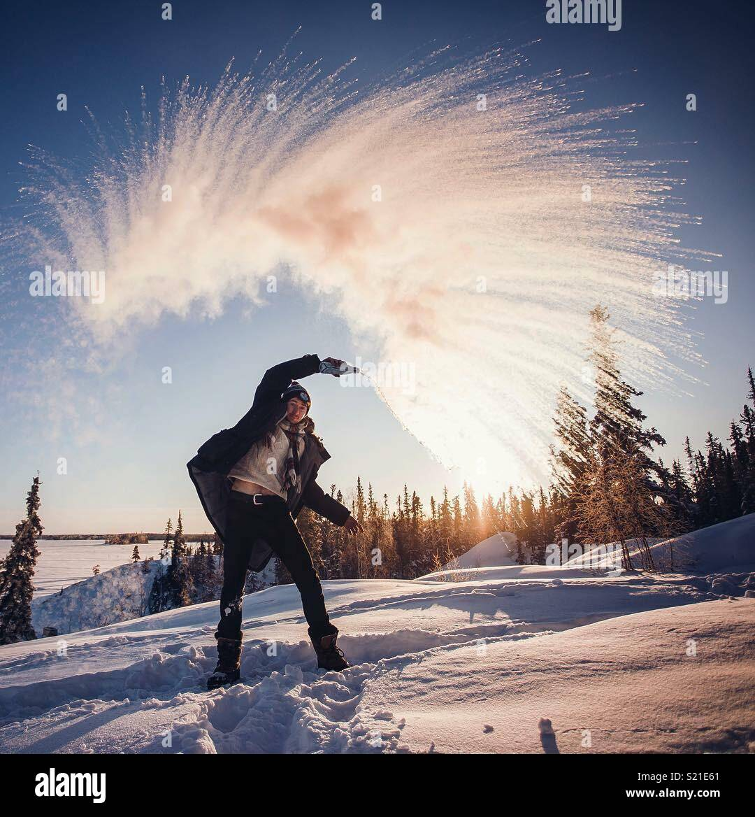 Throwing water in -40C which instantly freezes.  Northwest Territories, Canada - Stock Image