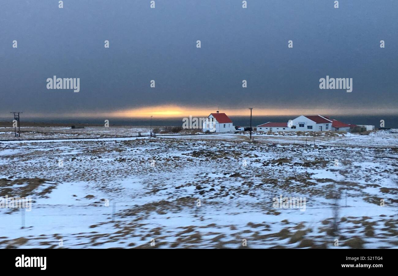 Lone house in snow covered fields at sunset - Stock Image