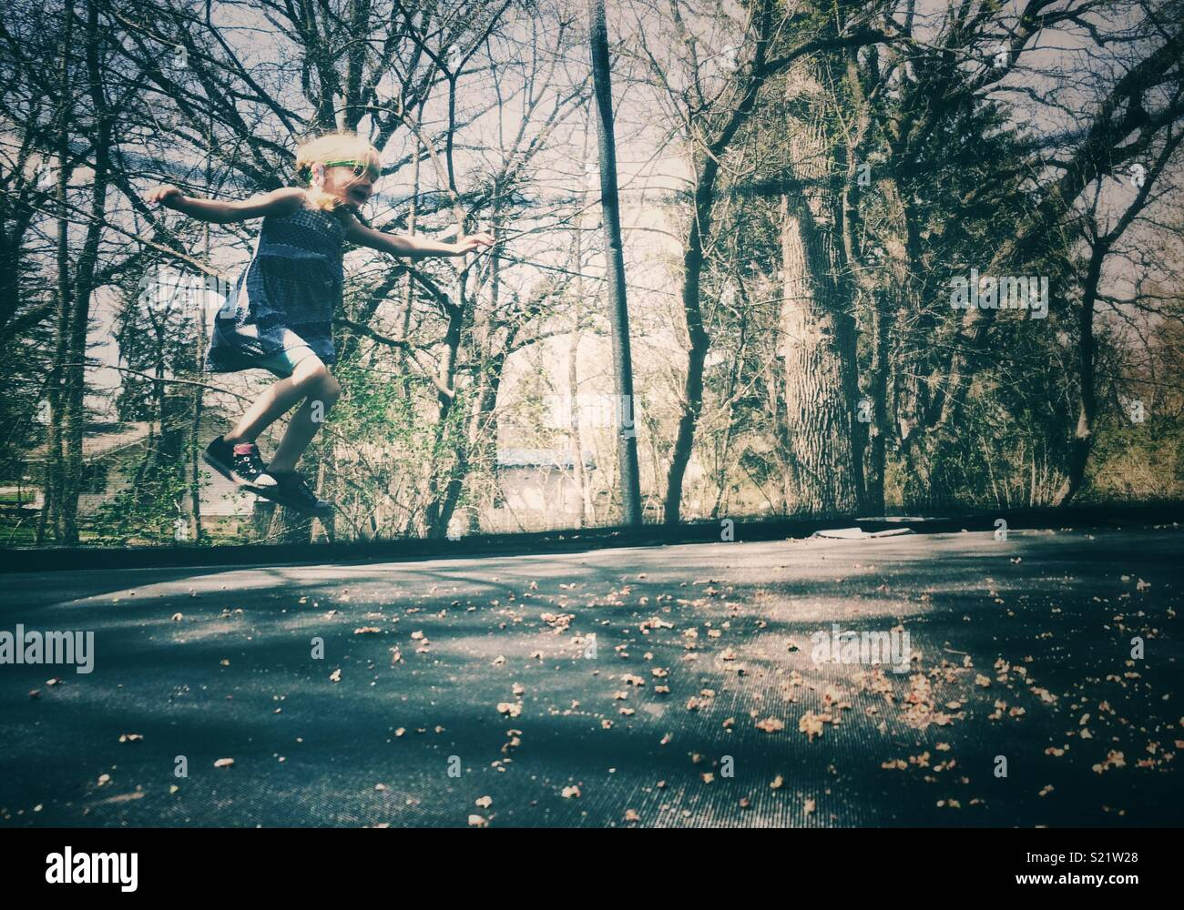 Girl bouncing on a trampoline - Stock Image