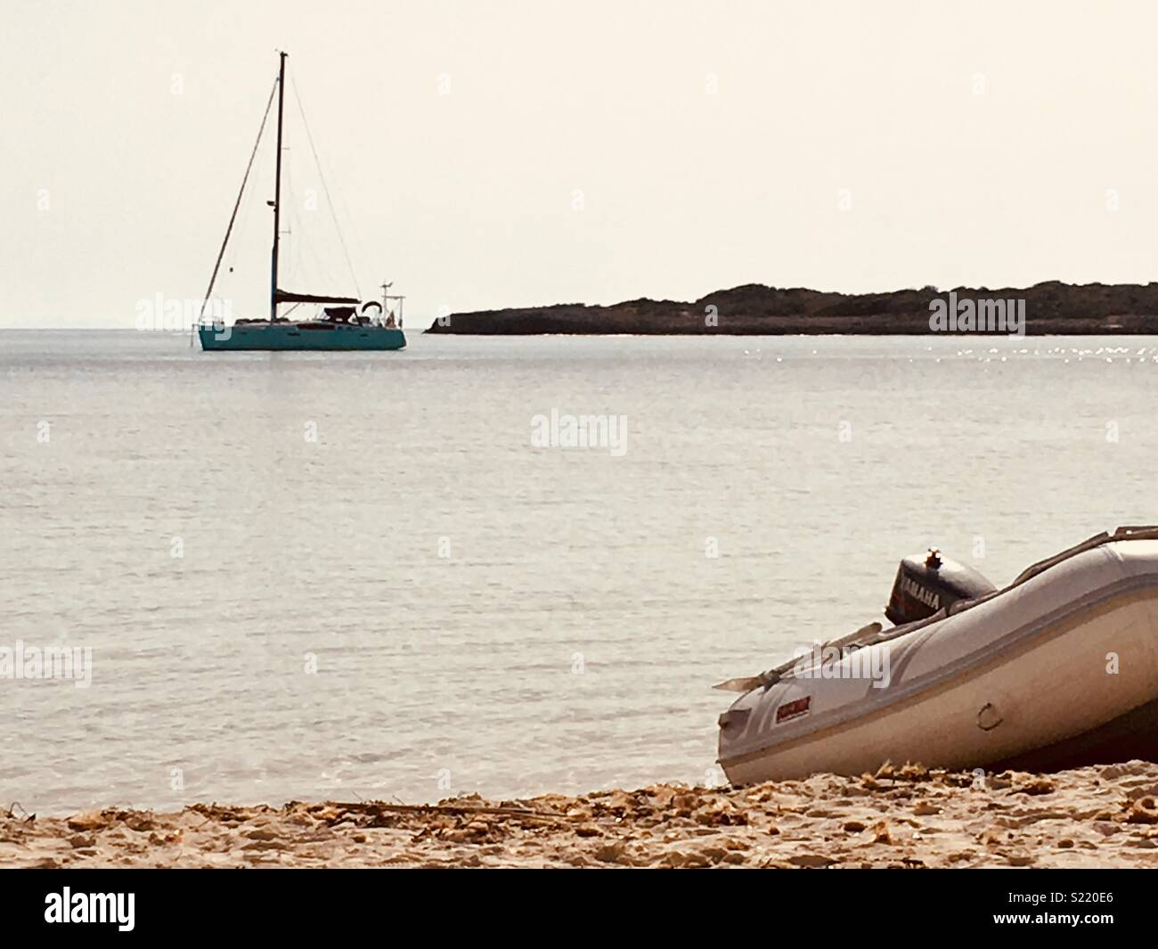 Our boat anchored in Son Saura and our dinghy on the beach - Stock Image