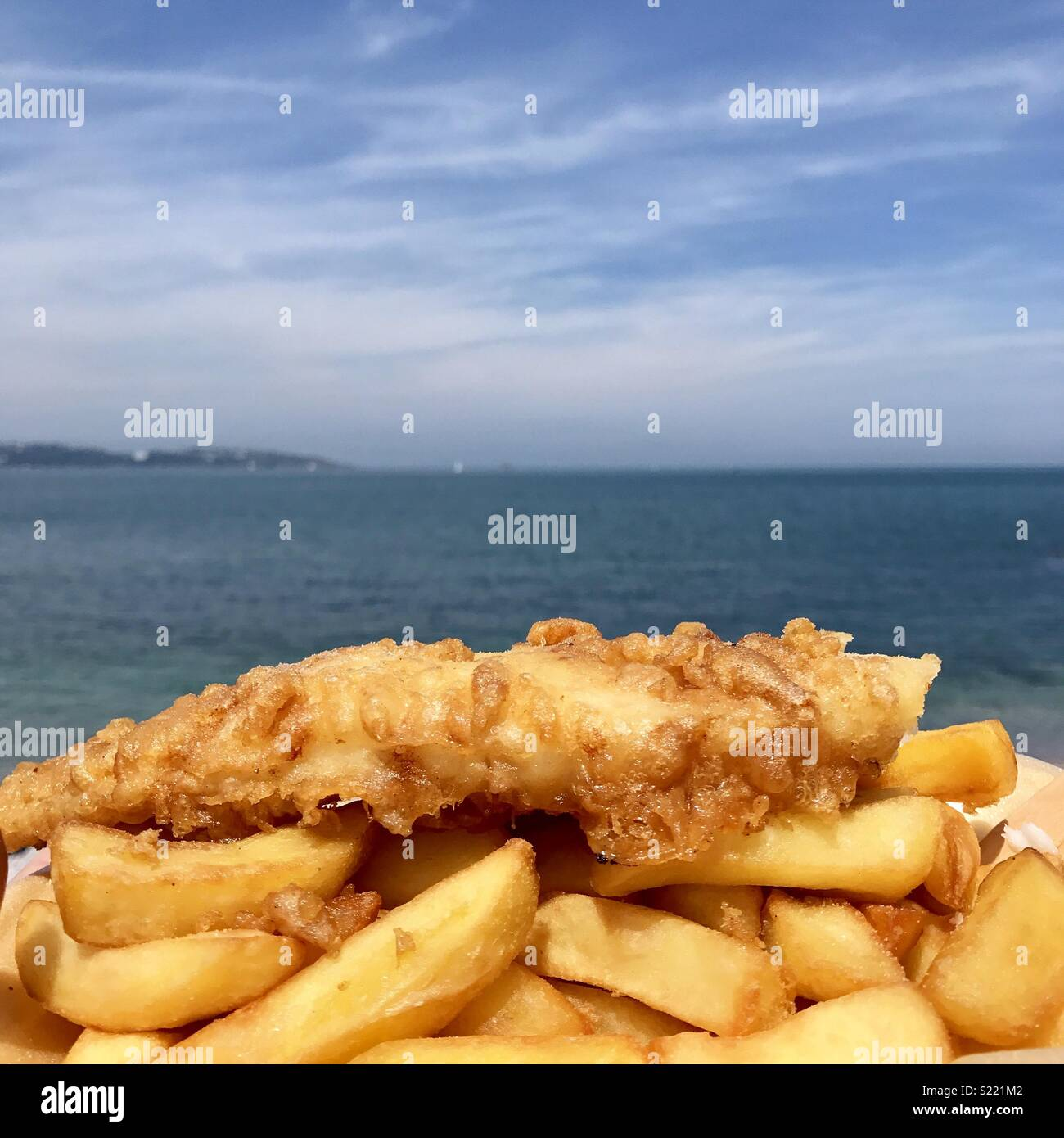 Fish and chips at the seaside in Brixham, Devon. - Stock Image