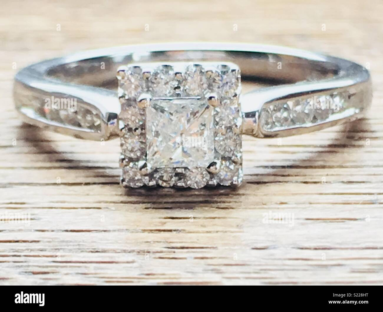 f862d4dfda6489 This elegant 18ct white gold ring is set with a sparkling princess cut  diamond solitaire surrounded by smaller twinkling diamonds.