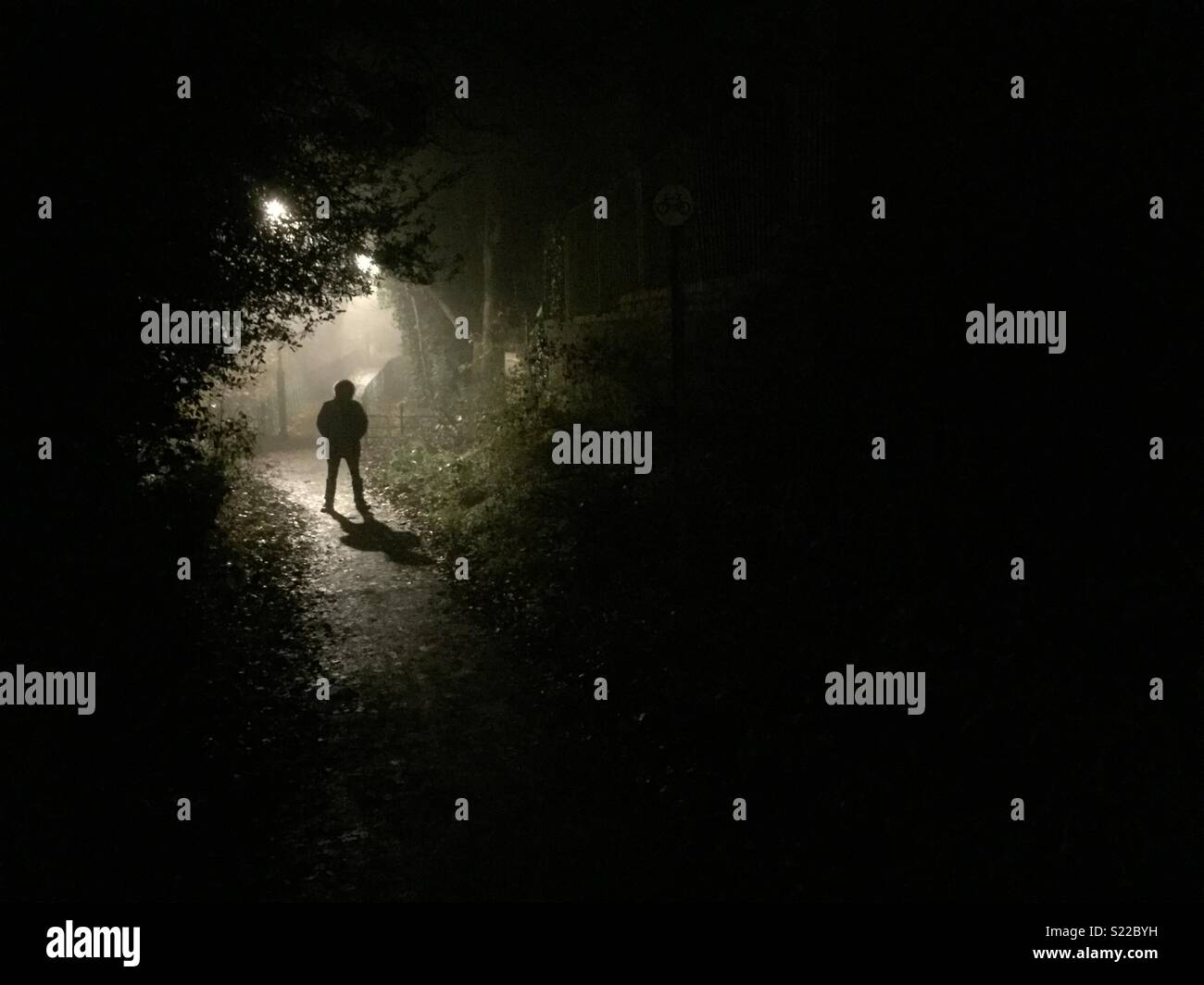 Stranger silhouetted at night. - Stock Image