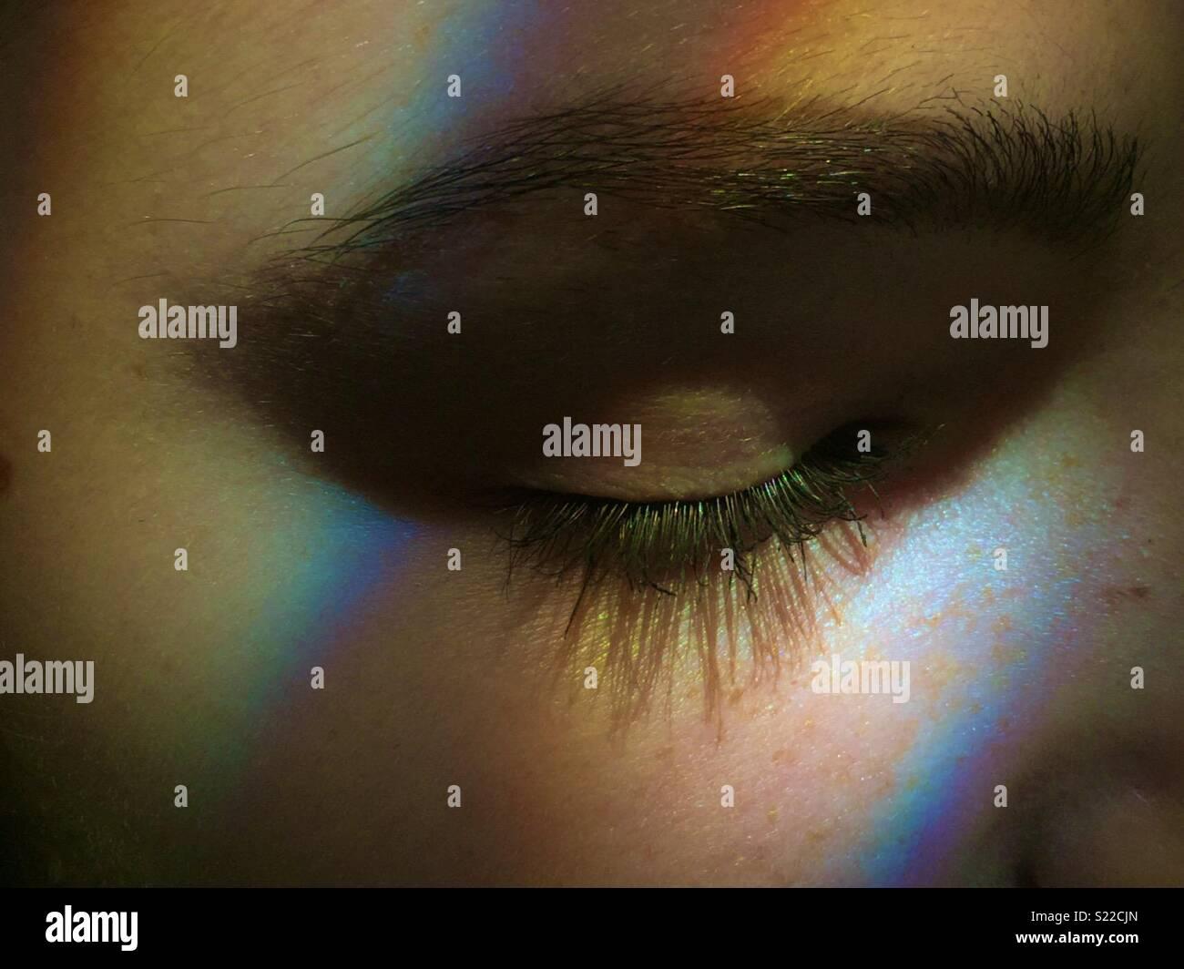 Girls eyelashes lit up with rainbow light - Stock Image