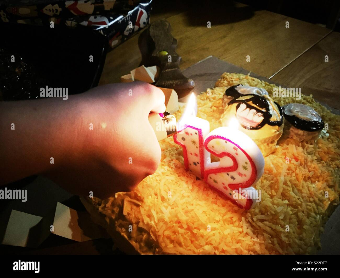 The hand of a twelve years old boy lighting the candles on his birthday cake - Stock Image