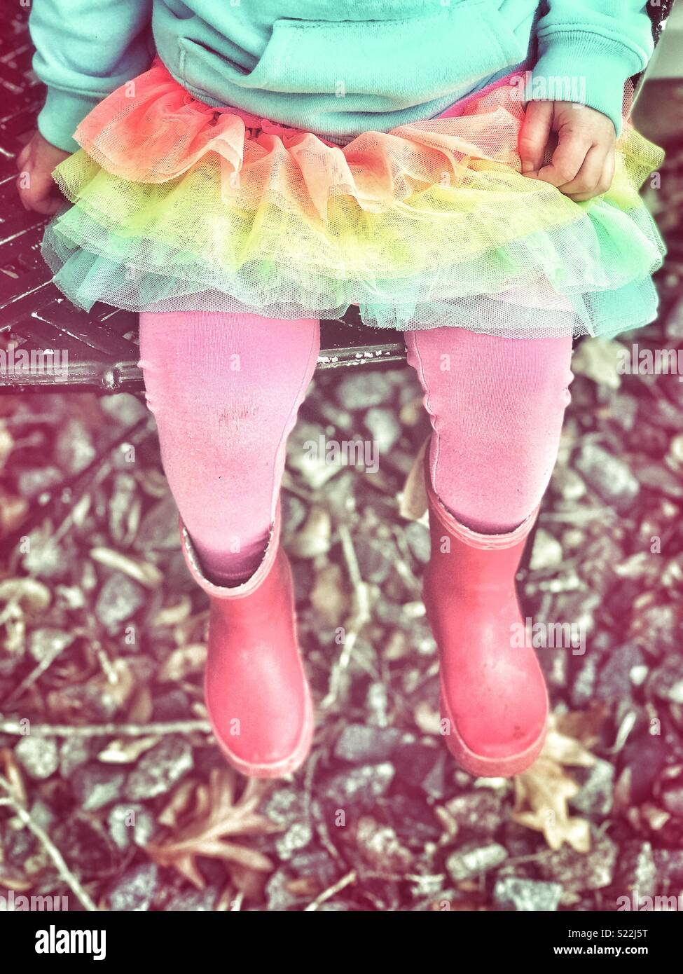 Little girl sitting on a chair outside with a tutu, pink tights and red rain boots - Stock Image