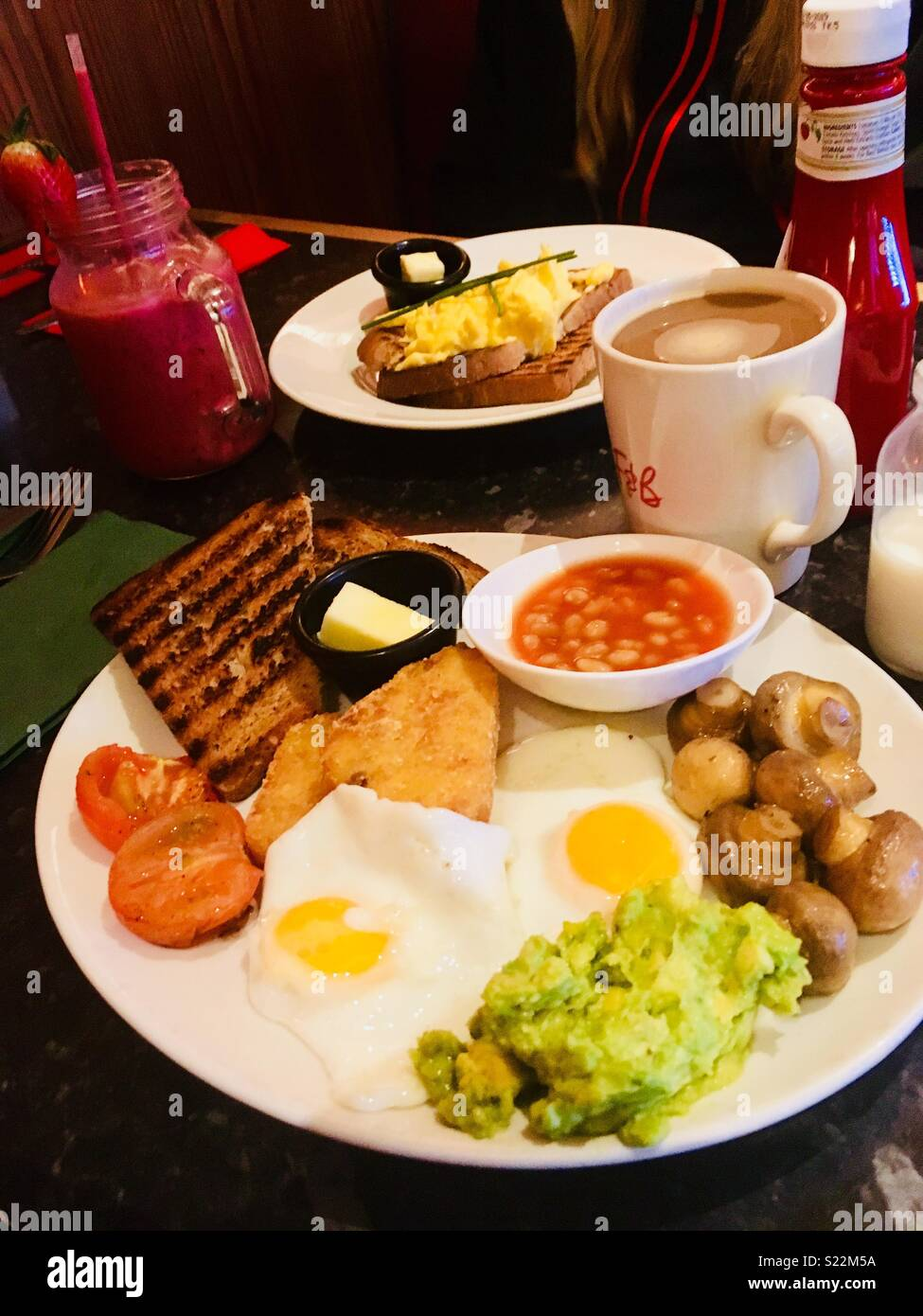 An  vegetarian English breakfast of eggs, hash browns, mushrooms, avocado mash, grilled tomato, toast and butter. In the background is ketchup, a smoothie and a mug of coffee. - Stock Image