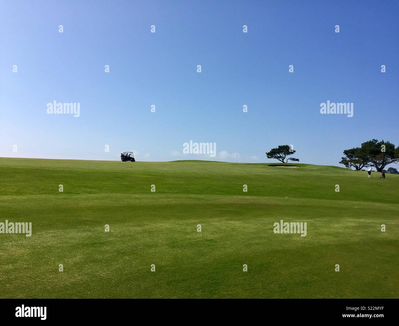 Beautiful clear blue summers day on a golf course, with a golf buggy on the horizon - Stock Image
