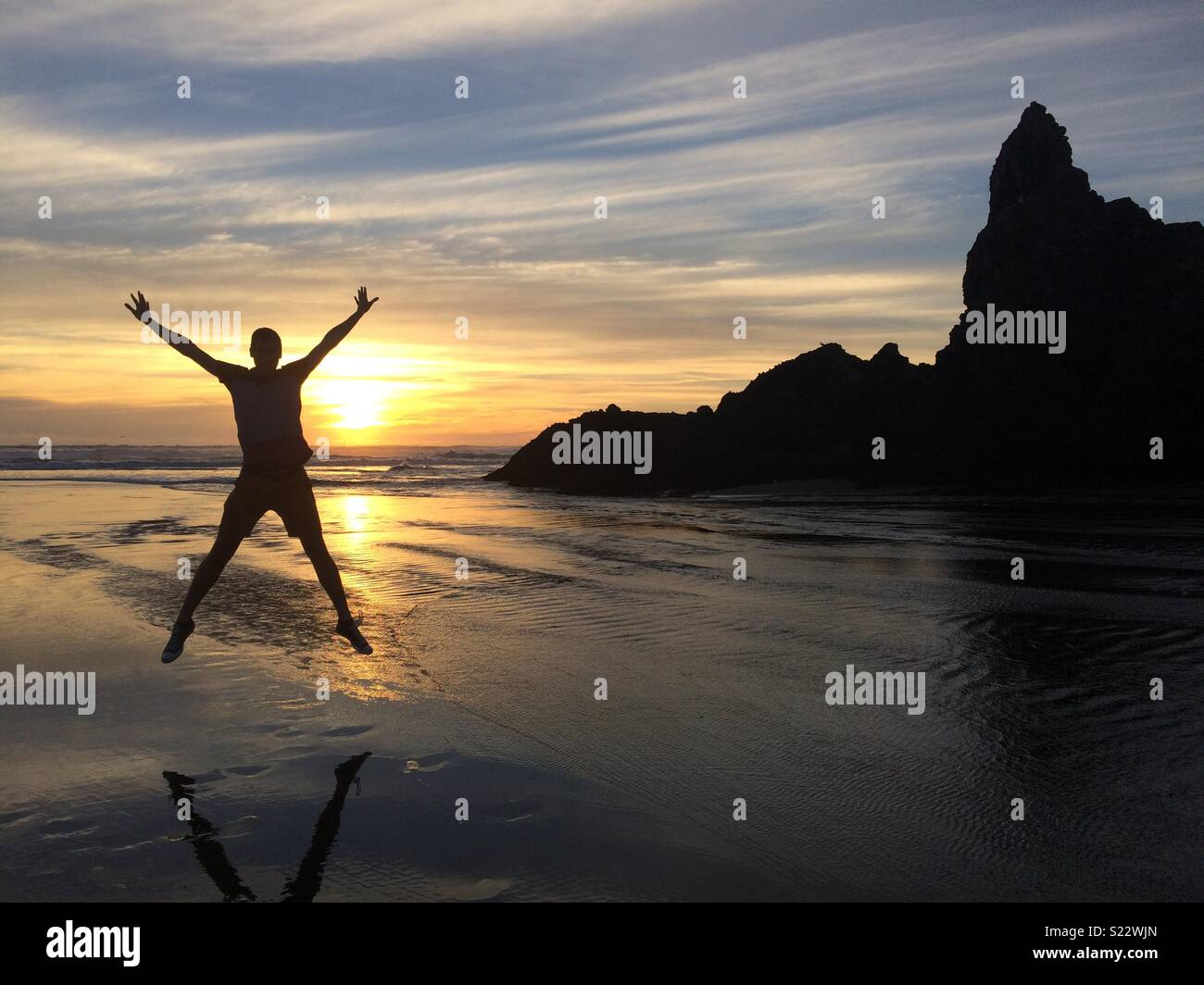 Sunset at Piha, Auckland, New Zealand showing man star jumping in front of mountain and sun - Stock Image