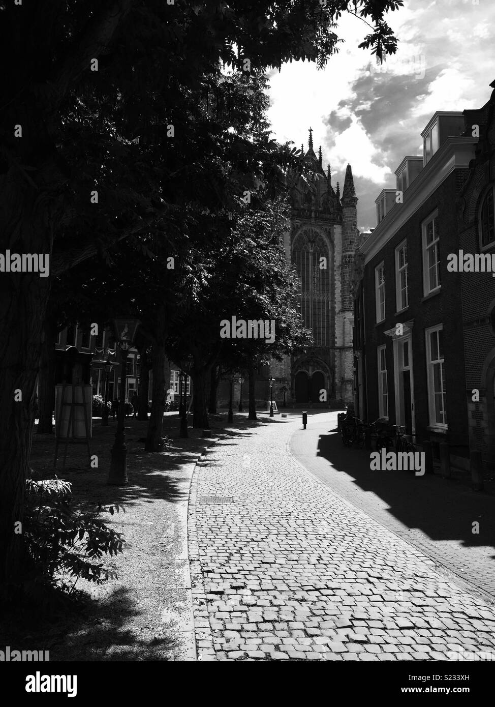 Beautiful side street leading to a cathedral captured on a sunny hot day in silver tone. - Stock Image