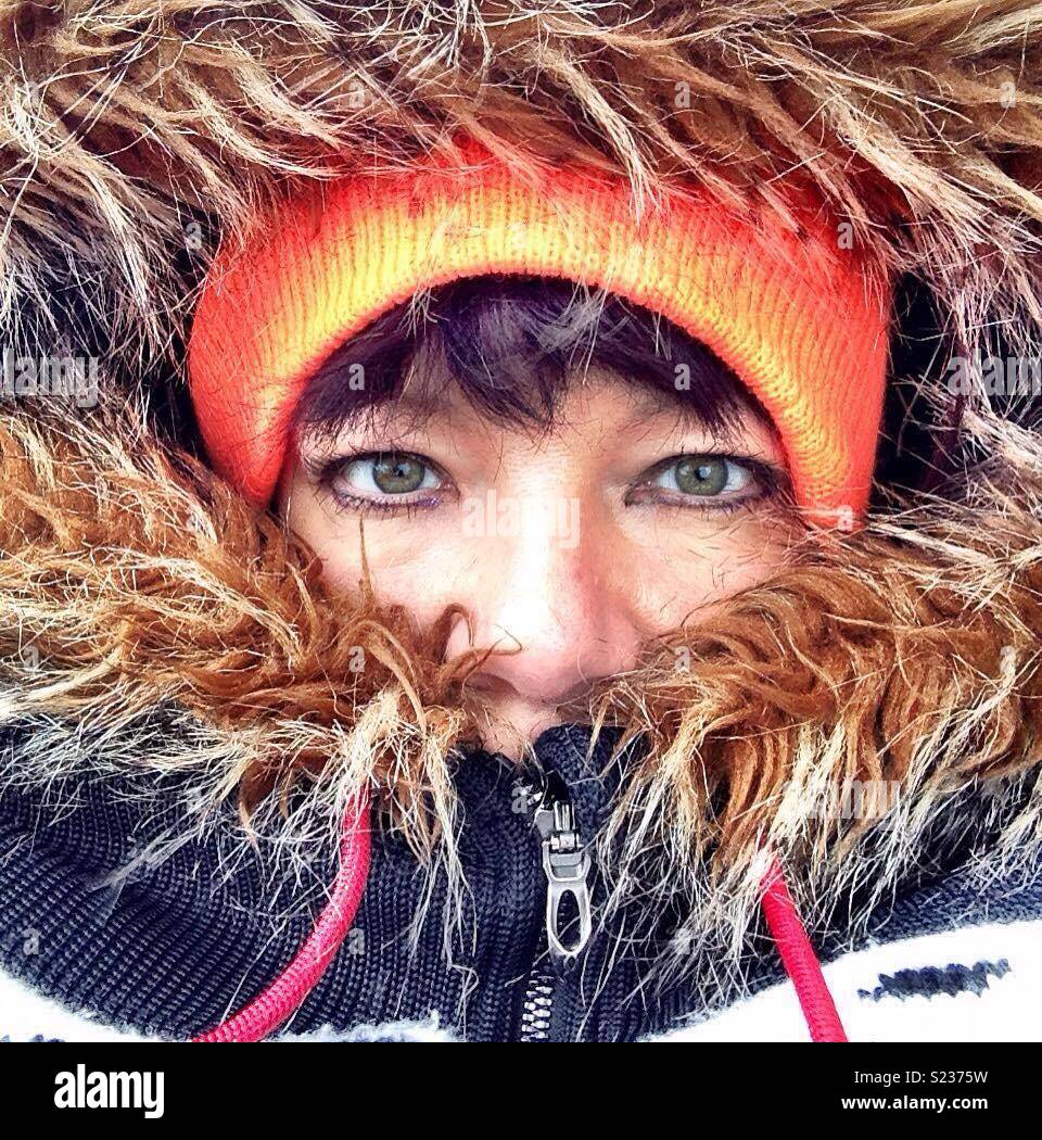 Woman with furry hood and orange hat. Eskimo features. Nose and eyes showing. - Stock Image