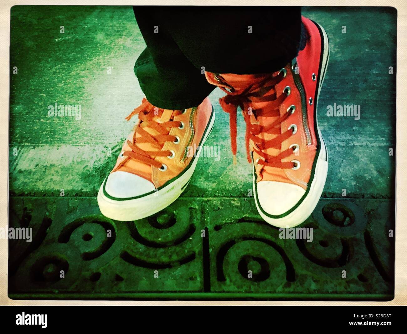 Dos grados línea Deshacer  Feet in orange Converse high tops on a ornate city grate Stock Photo - Alamy