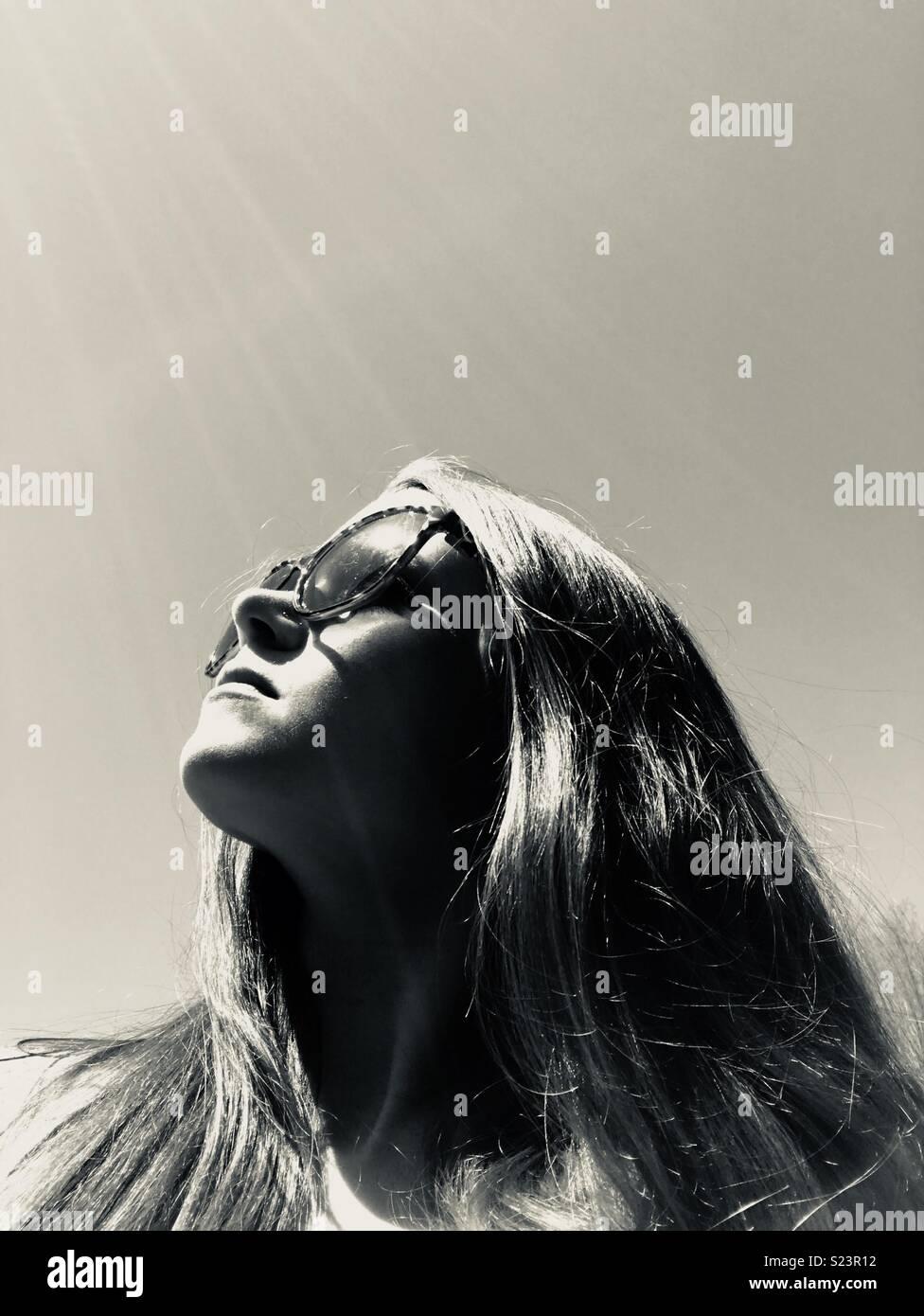 Sun shining down on girl with sunglasses - Stock Image