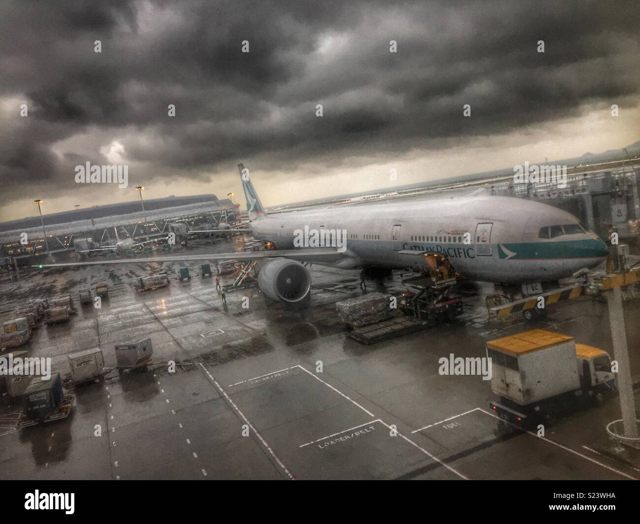 A Cathay Pacific Boeing 777 being loaded on the apron at Hong Kong International Airport - Stock Image