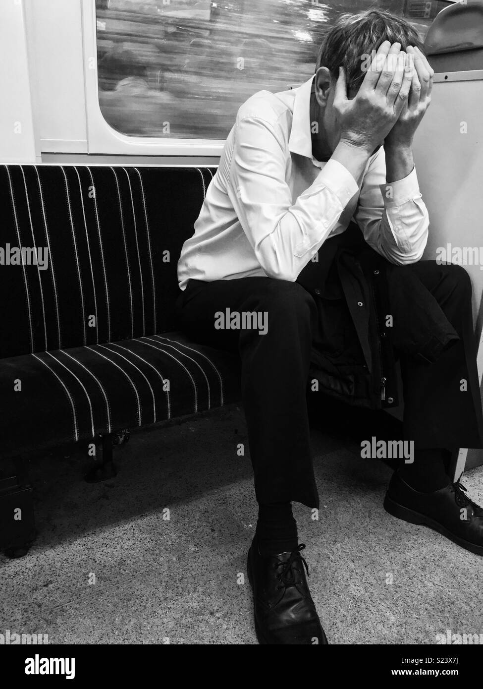 MAN SITTING ON TRAIN COVERING FACE WITH HANDS - Stock Image