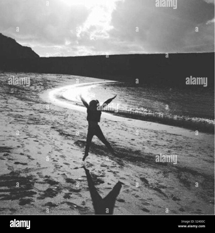 Star jump silhouette on beach - Stock Image