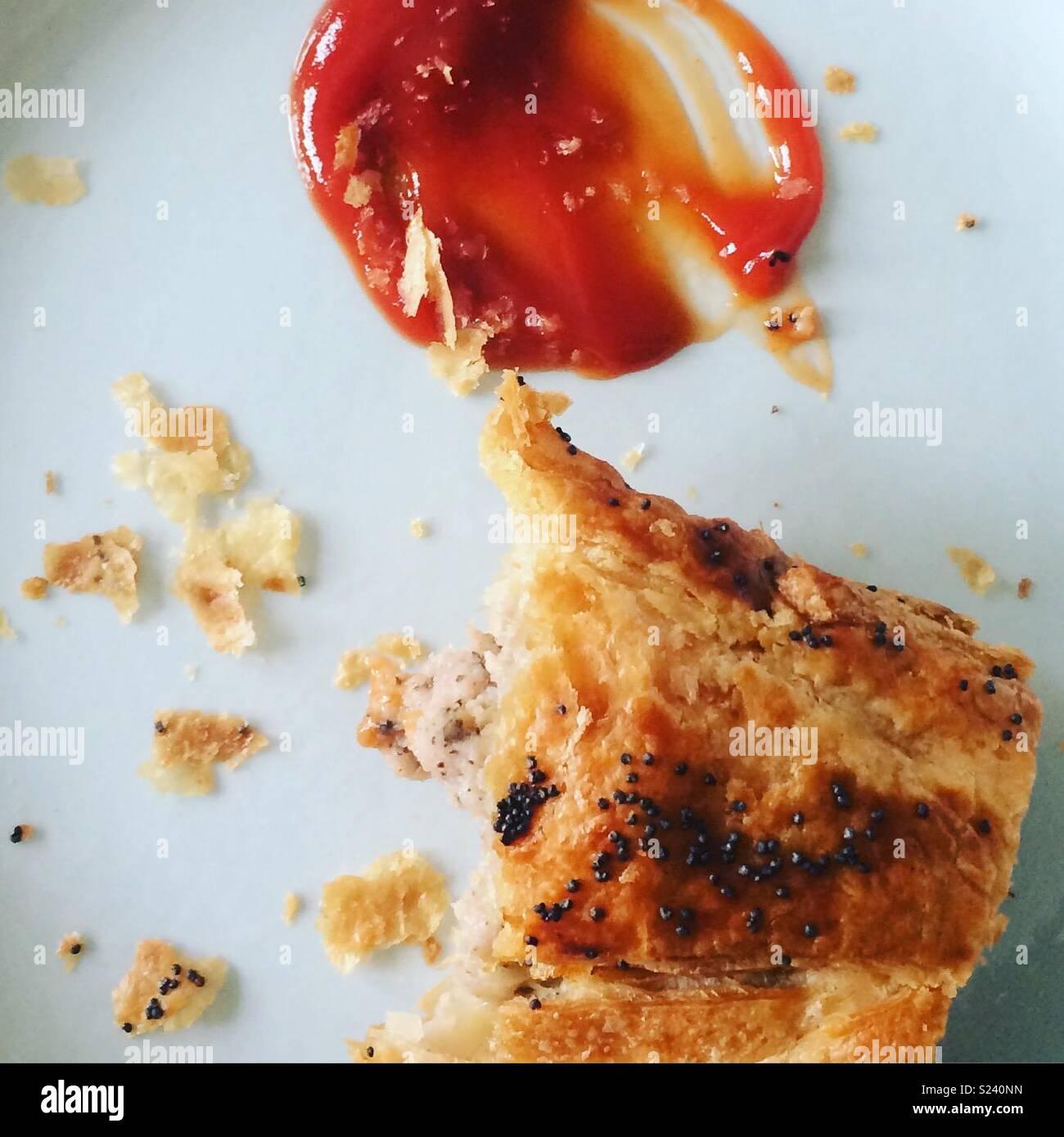 Posh sausage roll and ketchup. Half way through being eaten. - Stock Image