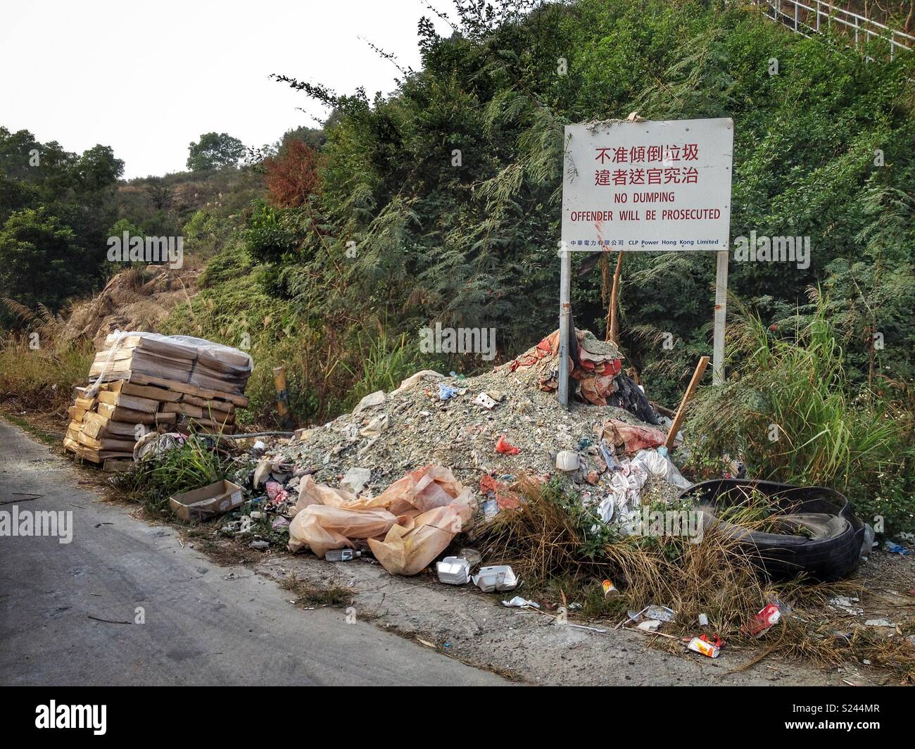 Bilingual 'No Dumping' sign in Chinese and English with illegally dumped building waste and a pallet of rotting fish, near the West New Territories Landfill, Nim Wan, Tuen Mun, Hong Kong - Stock Image