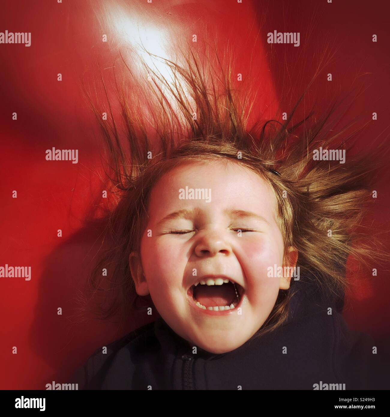 Toddler girl laughing with joy as she slides down a red slide - Stock Image