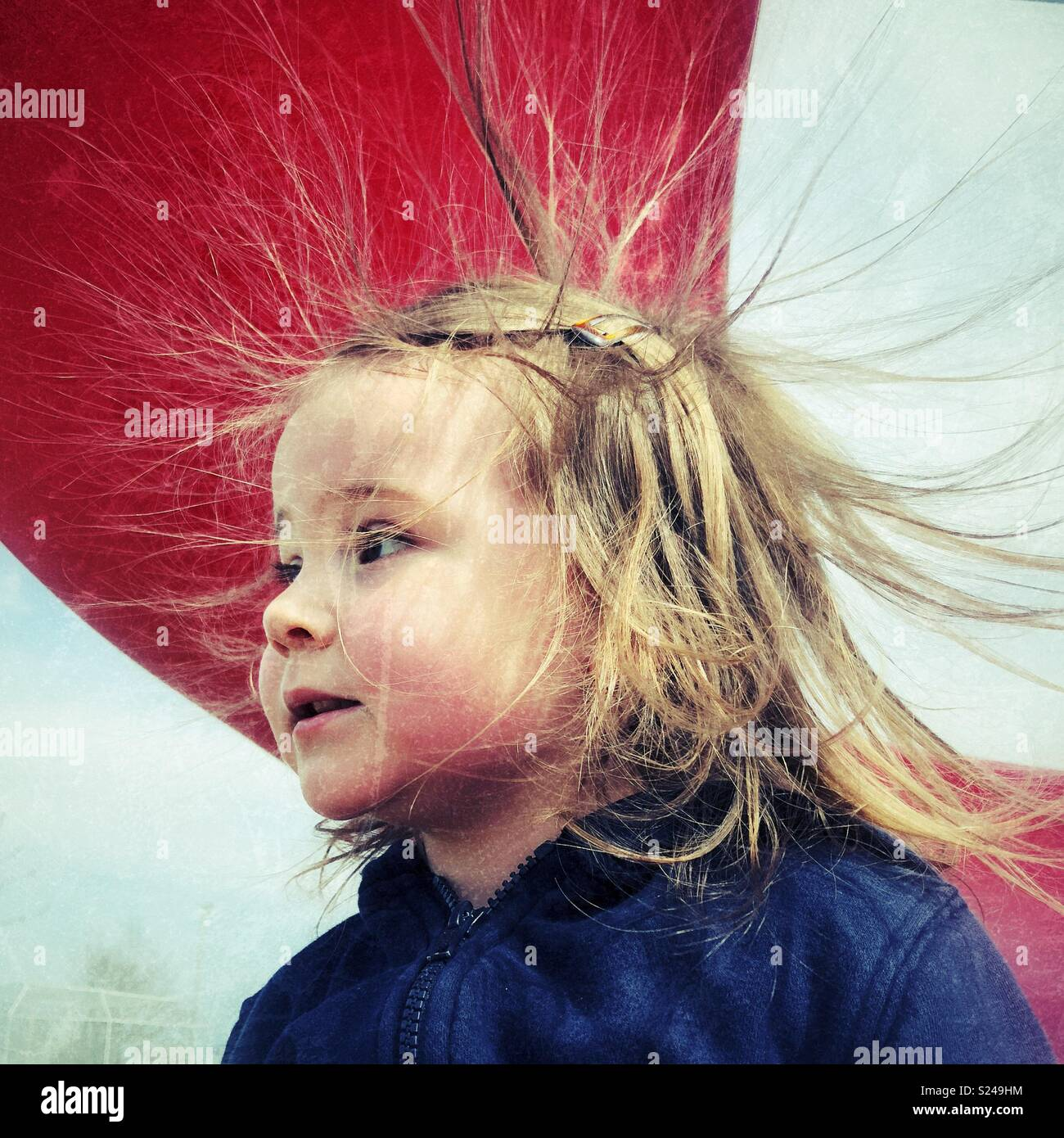 9d77c2c4e1 Young toddler girl portrait with static electricity from playground slide  causing hair sticking stick straight up