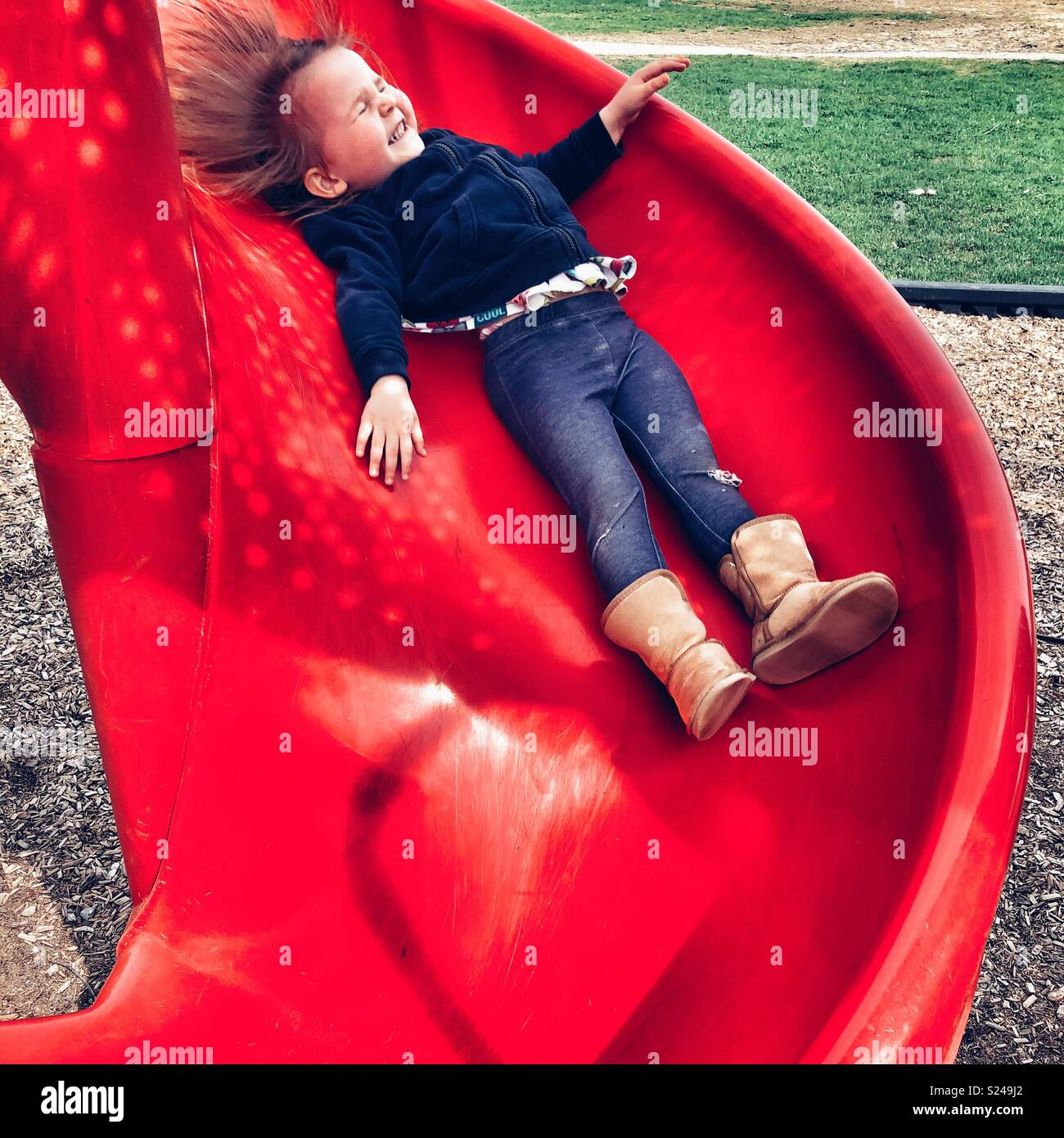 Toddler girl smiling happily while sliding down a red playground slide - Stock Image