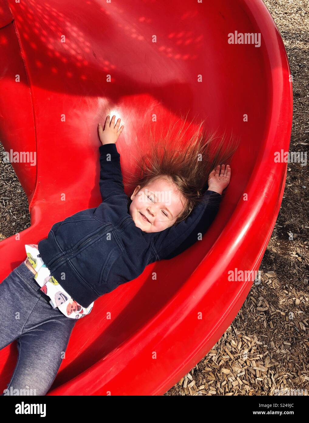 Action image of toddler girl sliding down red slide with arms up and hair sticking up - Stock Image
