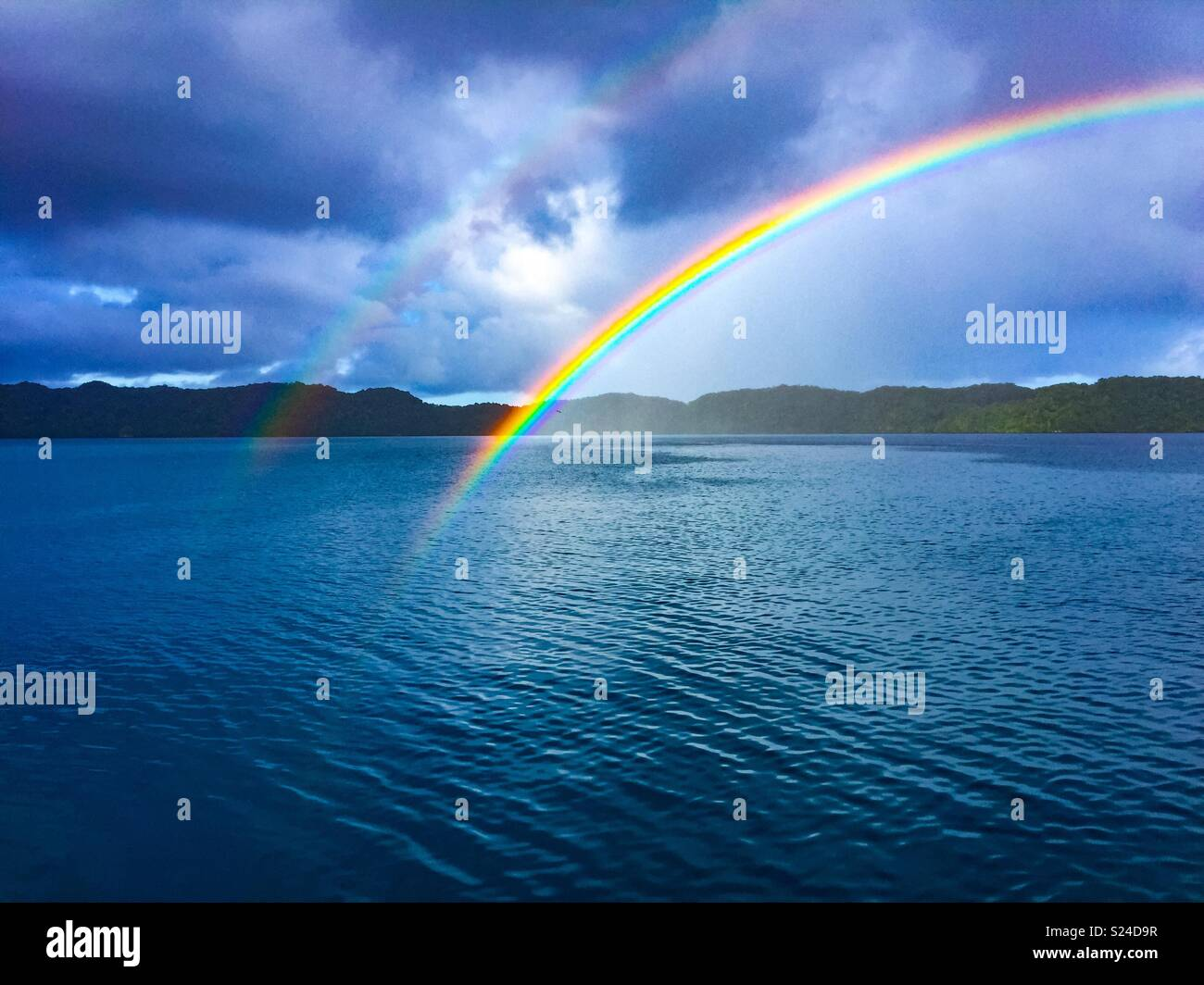 Twins rainbows rising from the lagoon after morning squall. In Palau - Stock Image