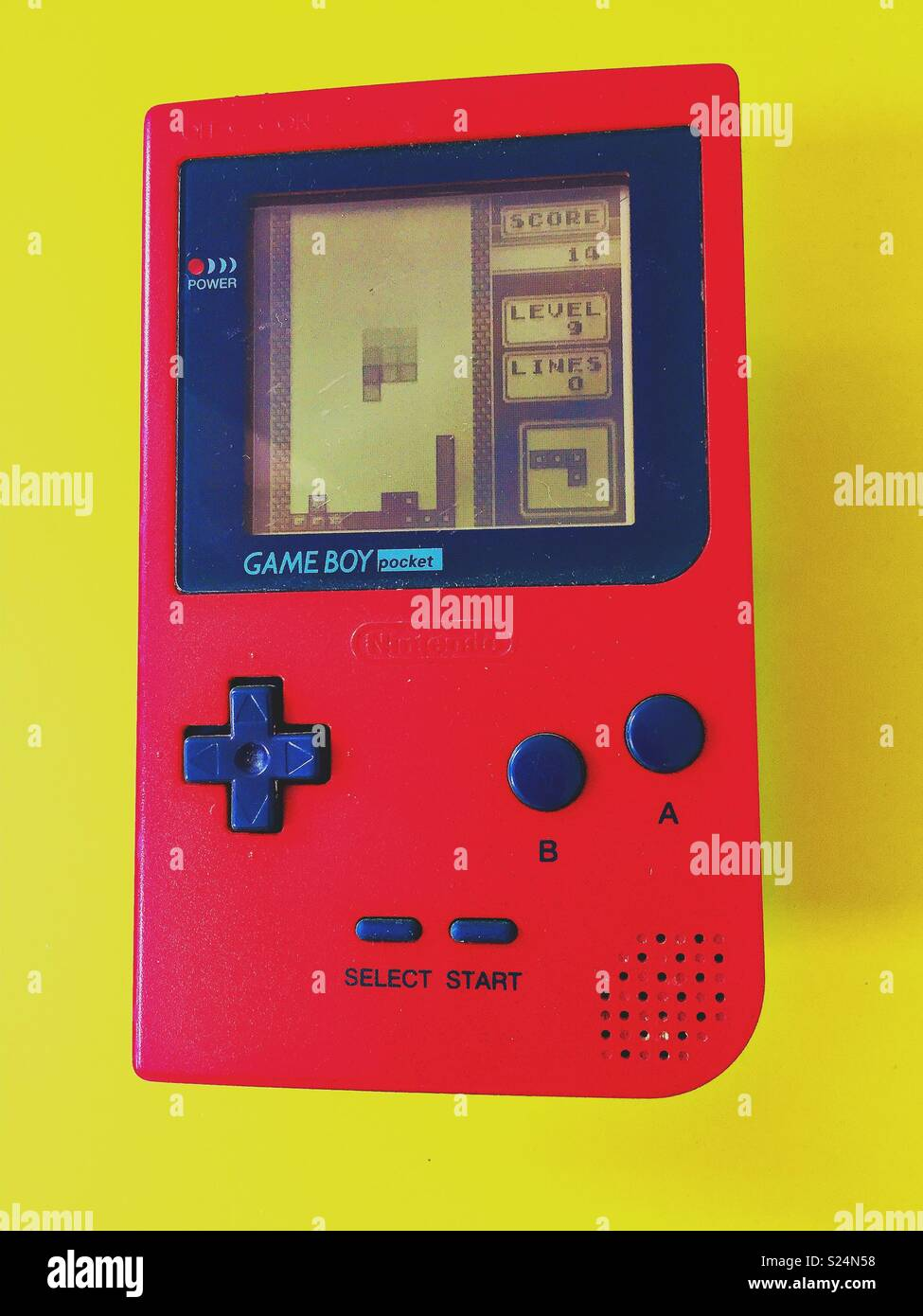 Red Game Boy Pocket against bright yellow background with Tetris