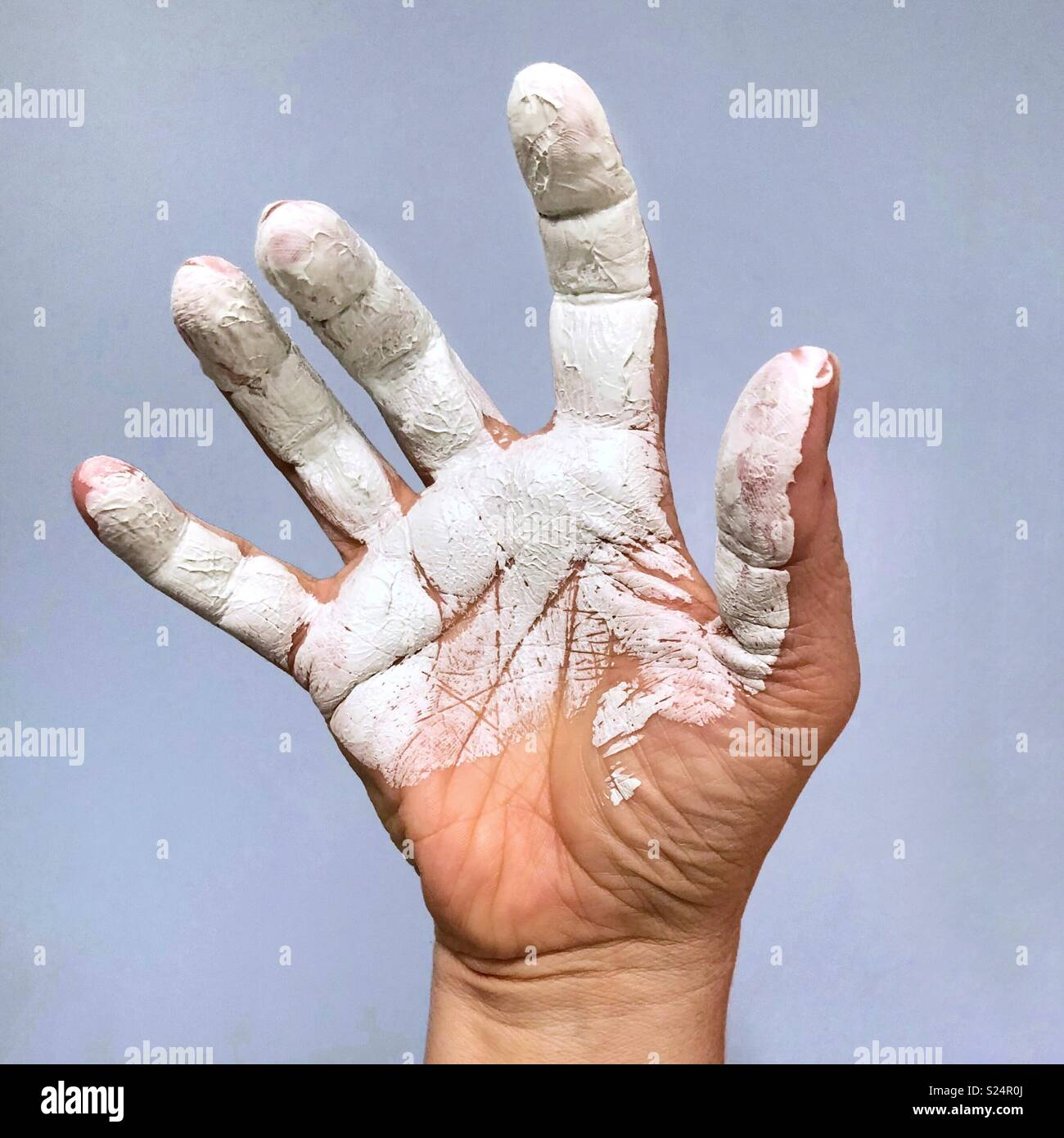 An outstretched hand with bended fingers covered in white paint Stock Photo
