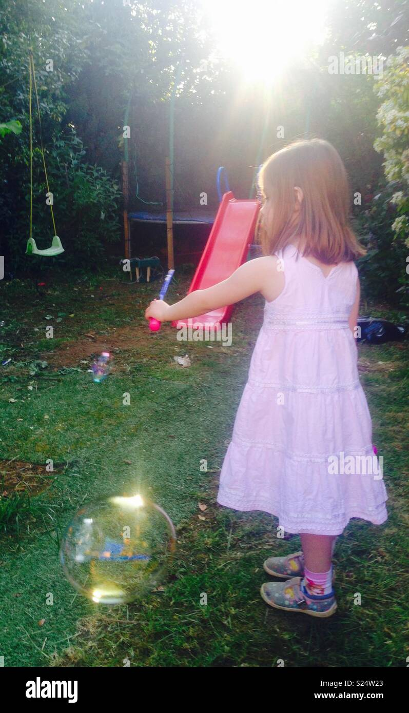 Little girl blowing bubbles in the garden with a low evening sun. - Stock Image