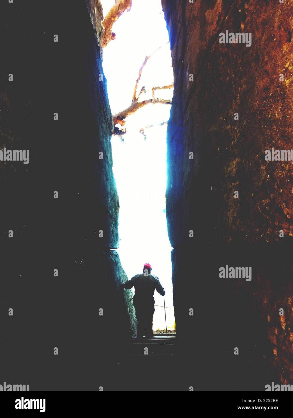 Hiker walks through rock chasm.  Exploring wilderness, silhouette person  being dwarfed by nature - Stock Image