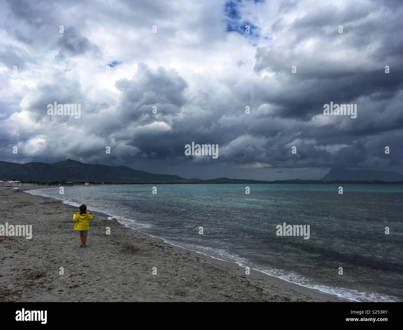 A boy running on the beach during stormy weather - Stock Image